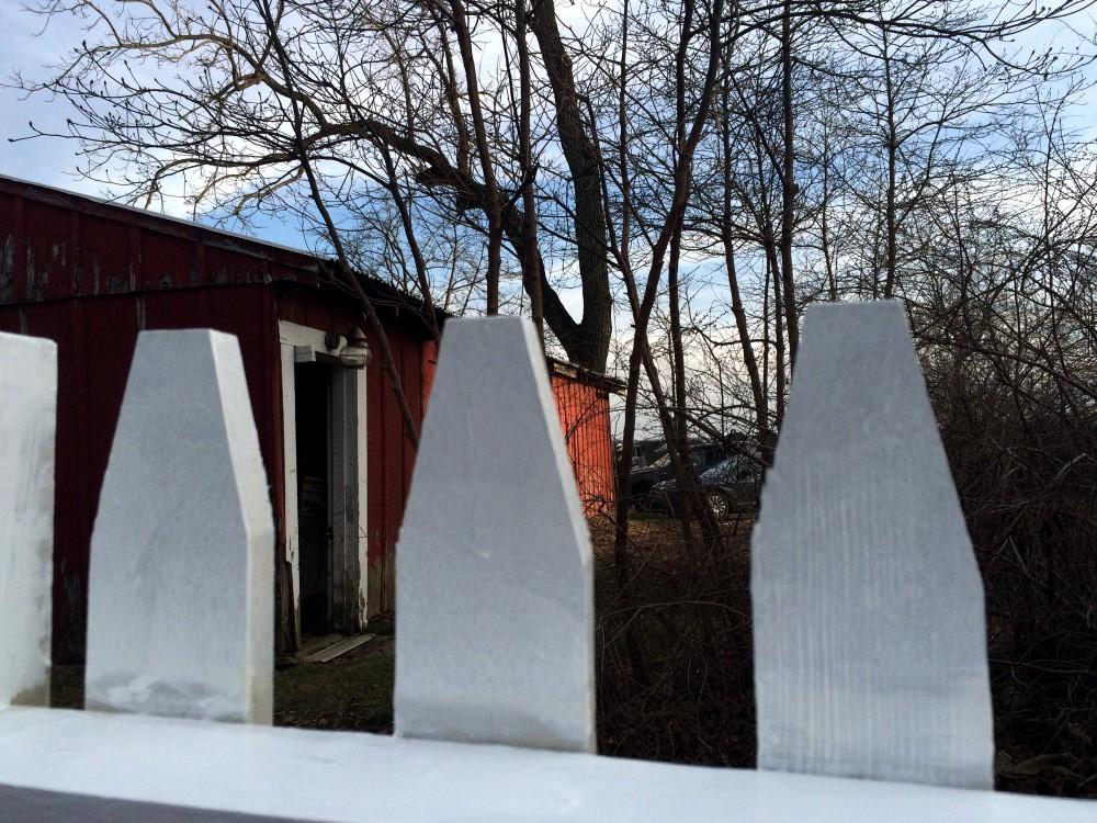 Red barn through white pickets